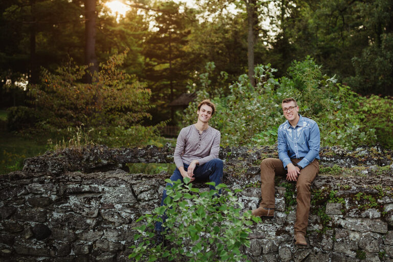 brothers posing together on a stone wall for photos at sunset