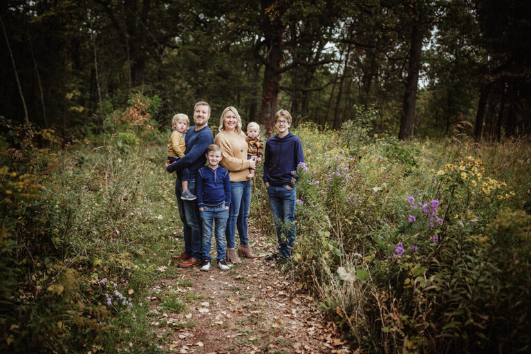 mom and dad with their four boys posing for a family photograph on a beautiful nature path filled with wildflowers in the fall