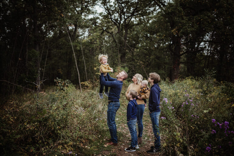 family all looking at their brother while dad flies him like an airplane while posing for a family photograph on a beautiful nature path filled with wildflowers in the fall