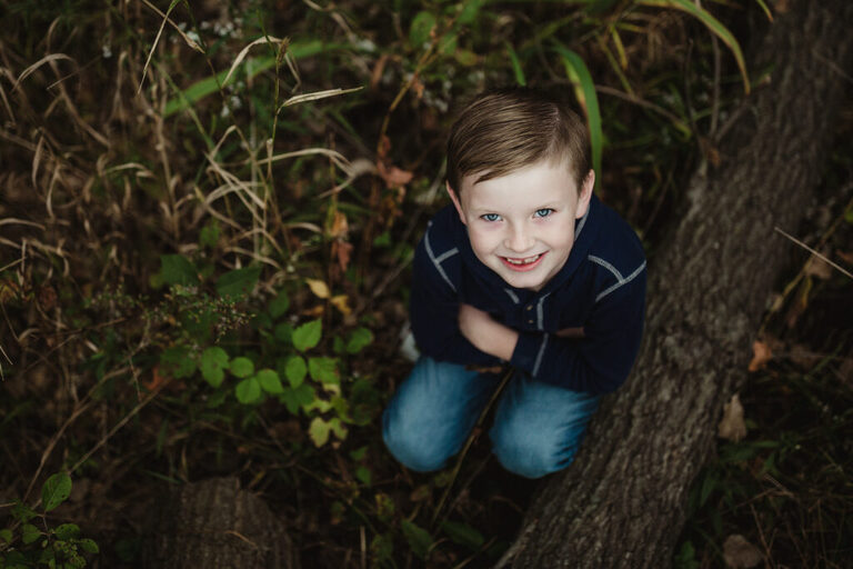 little boy crouched down next to a log in the forest as he looks up for a photo and smiles at the camera