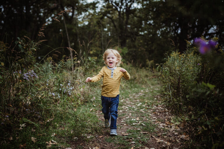 toddler boy running and laughing down a prairie path of wildflowers