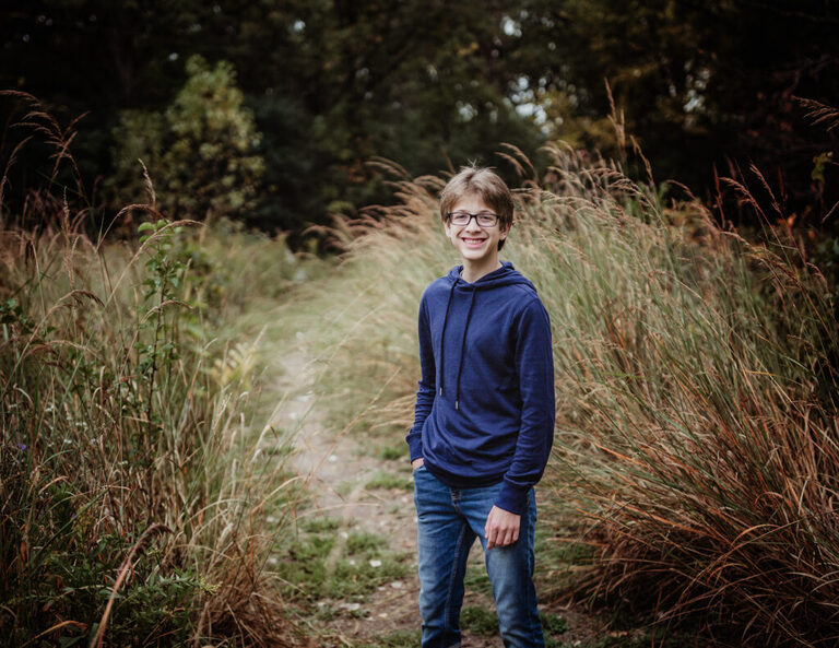 Freshman boy standing in the wild grass as he poses for a portrait