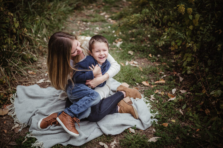 mommy squeezes and tickles her little boy as he wiggles on her lap