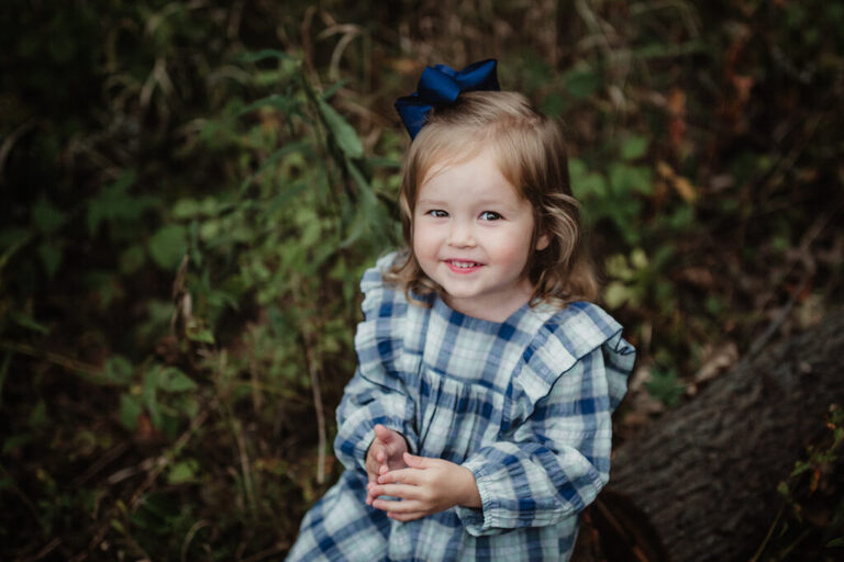 little girl sitting on a log in the woods looking up and smiling for the camera