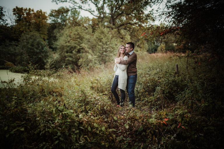 husband walks up behind his wife in the forest and embraces her in a giant hug