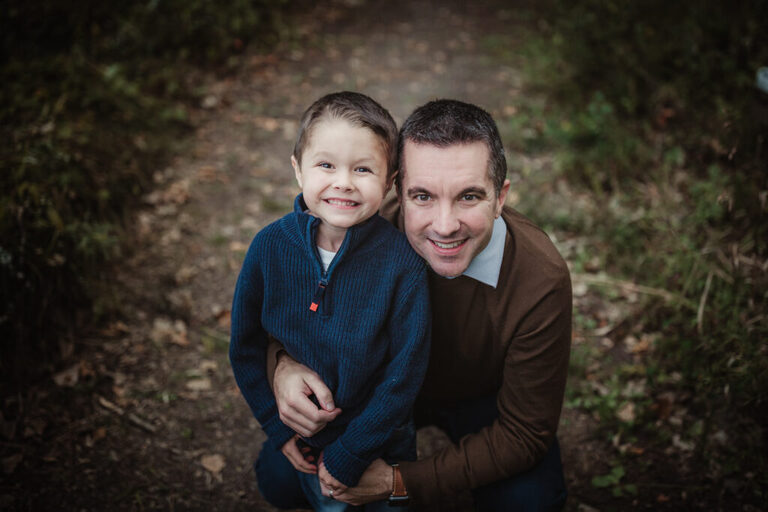 Dad crouches down next to his 5 year old son on a path filled with leaves