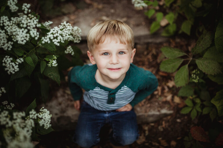 little boy sitting on stone steps surrounded by little white flowers looking up at the camera